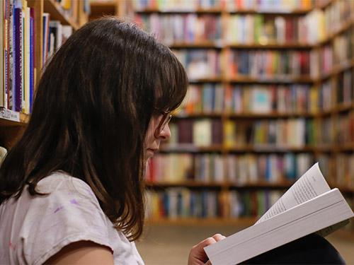 Junge Studentin lesend in einer Bibliothek