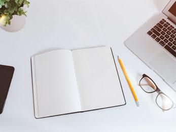 Notizbuch, Stift, Brille und Laptop