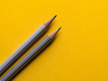 Zwei Bleistifte auf gelbem Grund