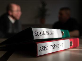 """Aktenordner zum Thema """"Sozialrecht"""" und """"Arbeitsrecht"""" liegen auf einem Tisch in den Räumen eines Beratungsbüros, Foto von Friso Gentsch; © picture alliance/dpa"""