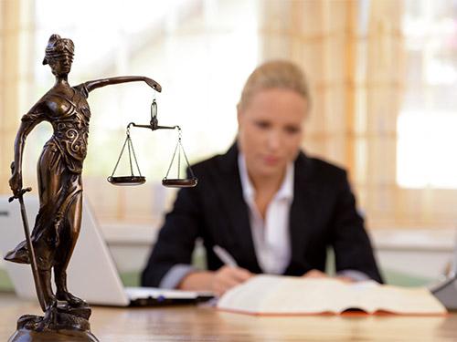 Anwältin bei der Arbeit, im Vordergrund eine kleine Statue der Justizia mit Waage und Schwert. © picture alliance / Erwin Wodicka/Shotshop